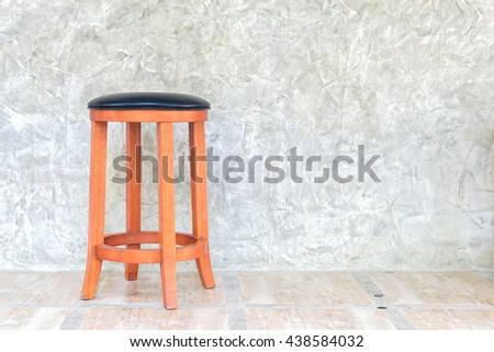 a chair with Grungy and smooth bare concrete wall texture - stock photo