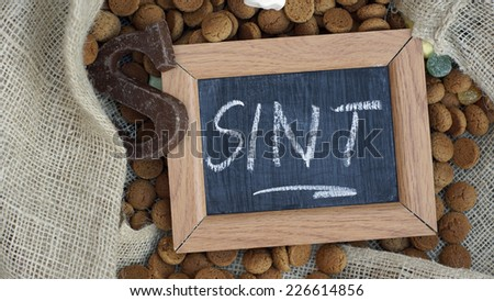 A chalkboard and a pile of Pepernoten, typical Dutch treat for Sinterklaas on 5 december - stock photo