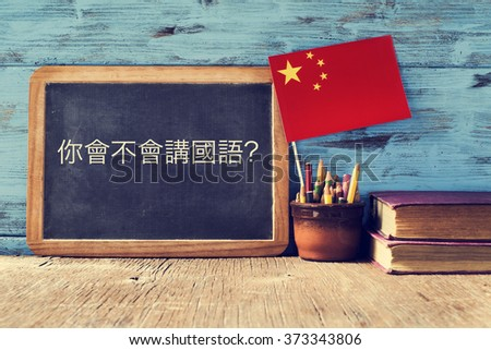 a chalkboard with the question do you speak chinese? written in chinese, a pot with pencils, some books and the flag of china, on a wooden desk - stock photo