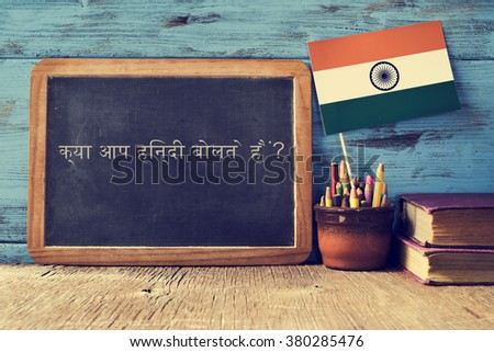 a chalkboard with the question do you speak hindi? written in hindi, a pot with pencils, some books and the flag of India, on a wooden desk - stock photo