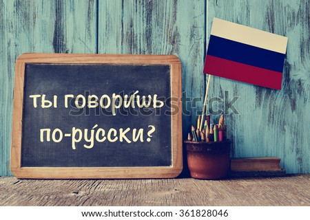 a chalkboard with the question do you speak russian? written in russian, a pot with pencils, some books and the flag of Russia, on a wooden desk - stock photo