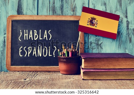 a chalkboard with the question hablas espanol? do you speak Spanish? written in Spanish, a pot with pencils and the flag of Spain, on a wooden desk - stock photo