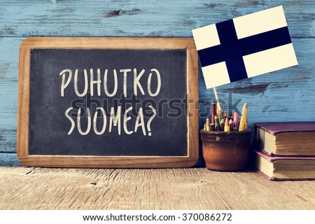a chalkboard with the question puhutko suomea, do you speak Finnish? written in Finnish, a pot with pencils, some books and the flag of Finland, on a wooden desk - stock photo