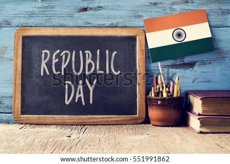 a chalkboard with the text Republic Day written in it and a flag of India, on a rustic wooden surface, against a blue wooden background