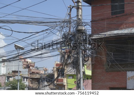 A chaos of electrical wires on a pole