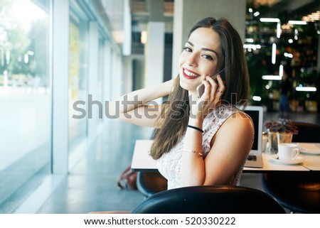 A charming female freelancer is talking on a phone while sitting in a cafe. Young attractive entrepreneur female is making a business call during the coffee break.