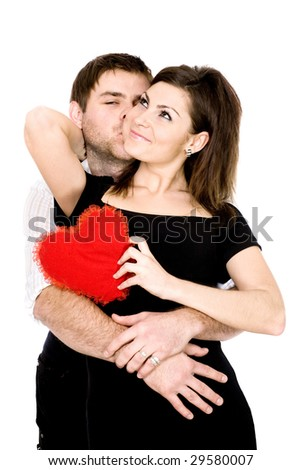 A charming young  woman standing with a scarlet heart in hands and a man giving  her a kiss - stock photo