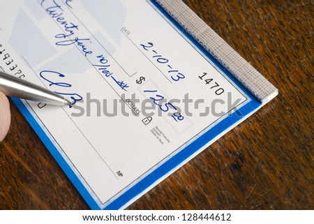 A Check is signed paying bills in ballpoint pen on the desk pay promise - stock photo