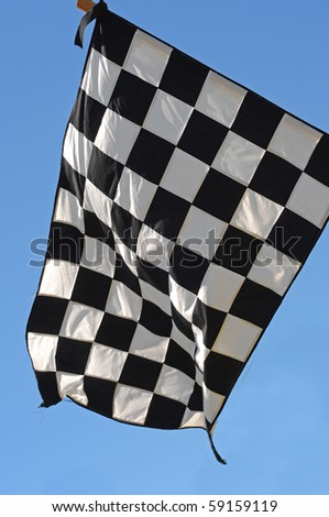 A checkered racing flag with a blue sky in the background. - stock photo