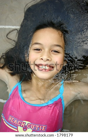 A cheerful and relaxed young girl half submerged in the swimming pool