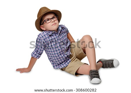 A cheerful boy sits on the floor and dreaming  against the white background. - stock photo