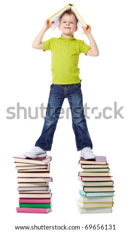 A cheerful boy standing on two heaps of books and holding a book over his head - stock photo