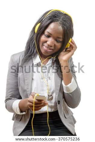 a cheerful charming African girl holding mobile phone and listening to music  - stock photo