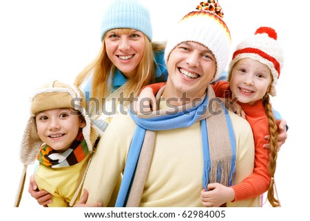 A cheerful family of four in winter clothes looking at camera