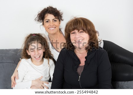 A cheerful grandmother with her daughter and her granddaughter Indoors - stock photo
