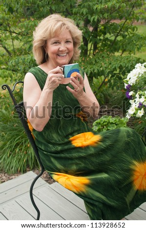 A cheerful mature woman enjoys a cup of coffee on the back deck of her lovely backyard. - stock photo