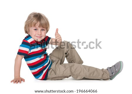 A cheerful preschool boy sits on the floor and holds his thumb up against the white background - stock photo