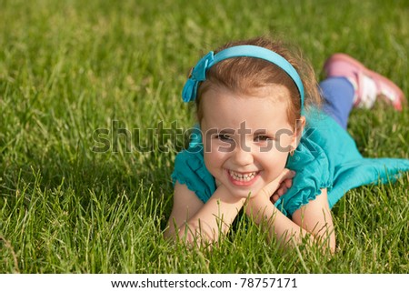 A cheerful smiling little girl is lying on the green grass