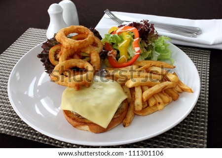 A Cheeseburger with french fries and salad - stock photo