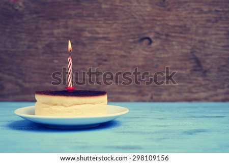 a cheesecake with a lighted birthday candle on a rustic blue wooden surface, with a retro effect - stock photo