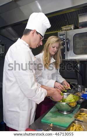 A chef and his sous chef picking salad from a strainer