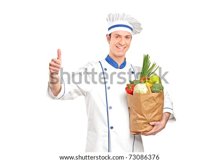 A chef giving thumb up and holding a grocery bag full with vegetables isolated on white background - stock photo