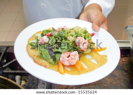 A chef holding a plate with a delicious shrimp salad - stock photo