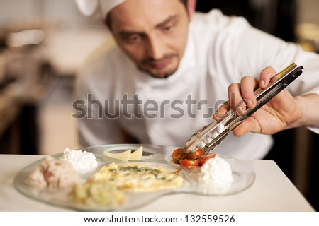 A chef placing slices of tomatoes  with help of a tong on final meal-plate. - stock photo