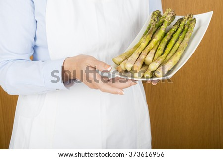 A chef showing a tray with fresh asparagus ready to cook - stock photo