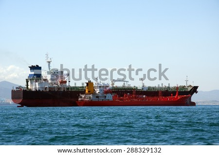 A chemical tanker which is anchored being refueled by a fuel barge at sea - stock photo