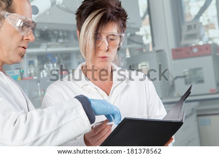 A chemist student is listing to her professor in the laboratory. - stock photo