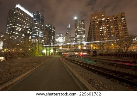 A Chicago railway with a skyline in the back on a dark night. - stock photo