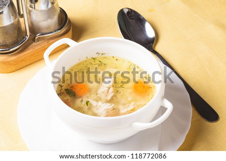 A chicken broth in white ware on the yellow tablecloth - stock photo