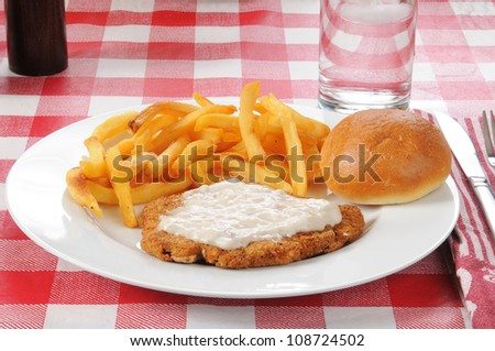 A chicken fried steak with french fries - stock photo