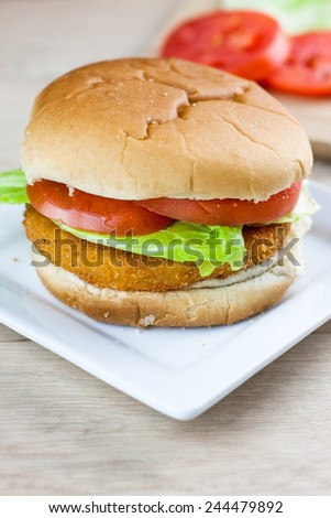 A chicken sandwich or hamburger with fresh tomato and lettuce on a white plate.