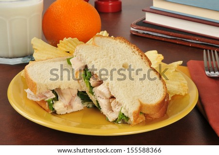 A chicken sandwich with potato chips, an orange and a glass of milk after school