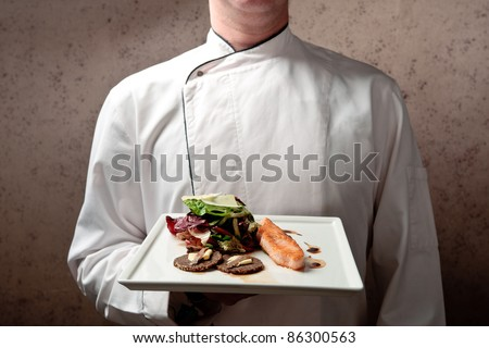 A chief dressed in white holding a white tray with roasted salmon fillet and vegetable salad elegantly decorated - stock photo