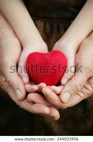 A child and grandparents hands holding a felted heart