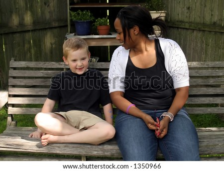 A child and his babysitter talking. - stock photo