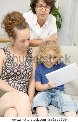 a child and his mother and his grandmother play with tablet