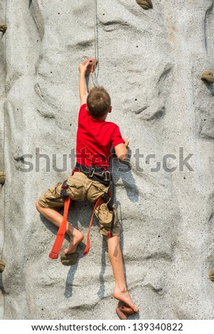 A child climbs on a rock-climbing wall - Tower - stock photo