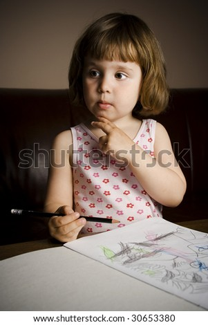 a child concentrating over her drawing