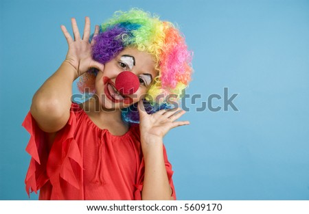 A child dressed in a clown costume playing the part.