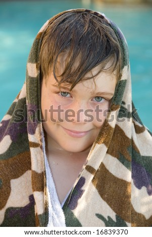 A child enjoys the summer by cooling off in a swimming pool. - stock photo