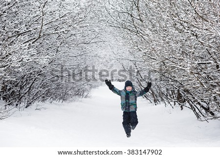 A child enjoys the winter and playing with snow outdoors. The joy and happiness of the boy in the winter forest. - stock photo