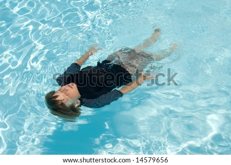 A child floats on his back in a fresh water swimming pool during a hot summer day.