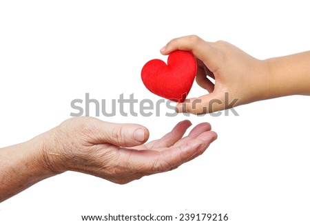 a child giving a red heart with the word love to an old female hand - Happy mother's day - stock photo
