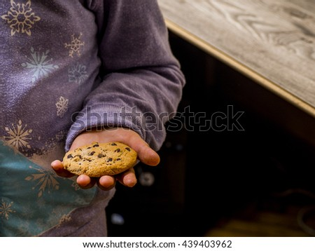 A child holding a cookie in a hand