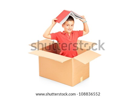 A child in a cardbox holding a book over his head isolated on white background