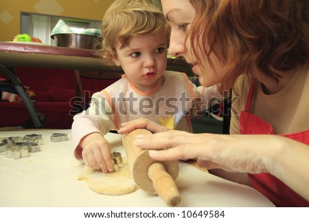 A child is helping mom to prepare the cookies. - stock photo